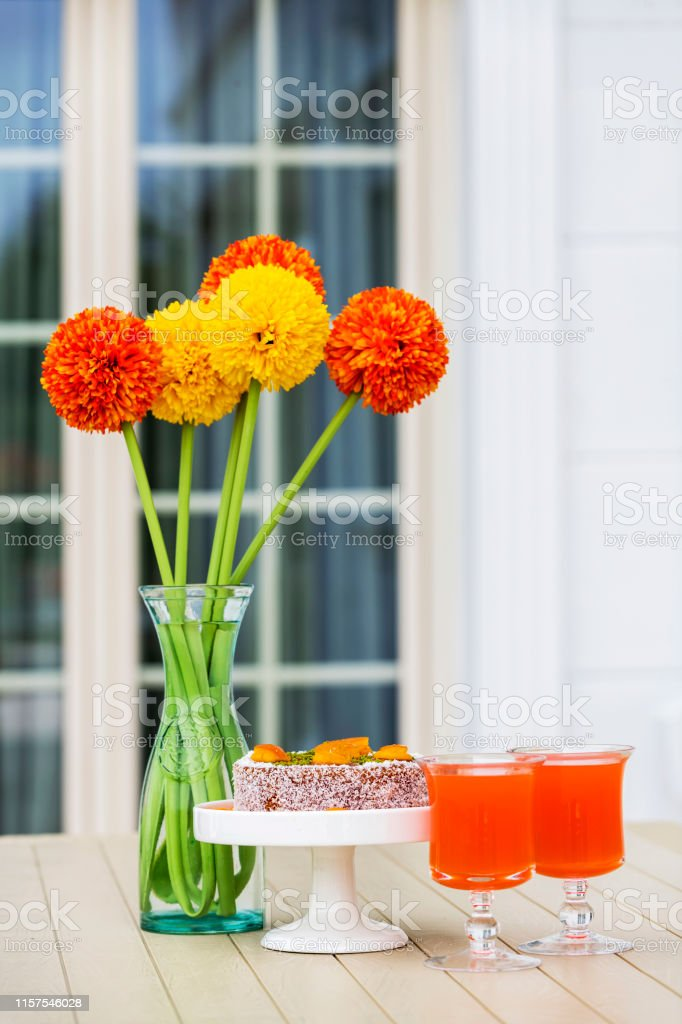 Colorful artificial flowers in glass vases in front of glass door.