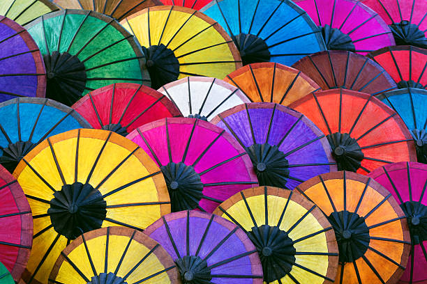Colorful Asian Umbrellas on Night Market in Luang Prabang, Laos Colorful handmade Asian umbrellas on display at night market in Luang Prabang, Laos. asian market stock pictures, royalty-free photos & images