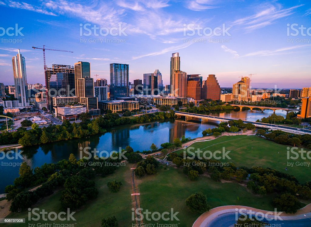 Colorful Austin Texas Skyline Aerial Golden Sunset Colorful Austin Texas Skyline Aerial Drone Shot Golden Sunset with a dramatic Sky of color. The Colorado river or Town Lake or Lady Bird Lake reflects the tranquil cityscape across the capital cities Texas Hill Country Landscape. Austin is now one of the top travel destinations and best places to live in America.  Aerial View Stock Photo