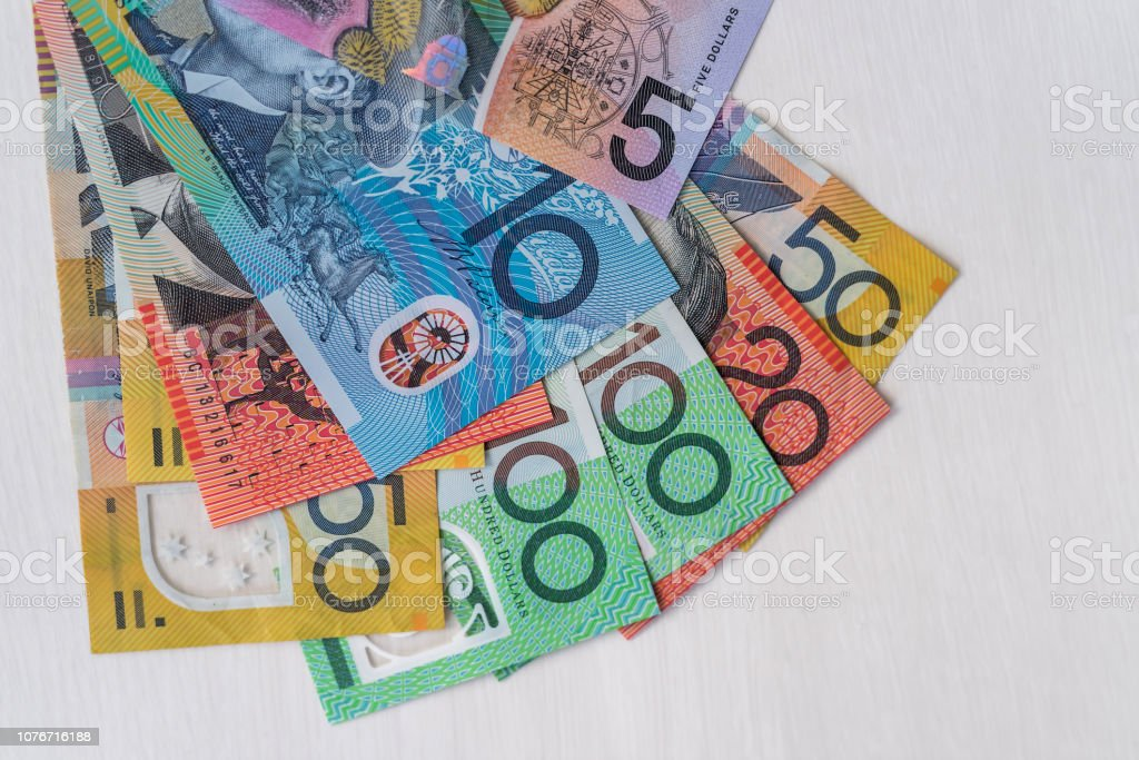 Colorful australian dollars laying on wooden table stock photo