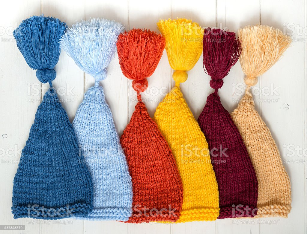 colorful baby knitted hats folded in row on table stock photo