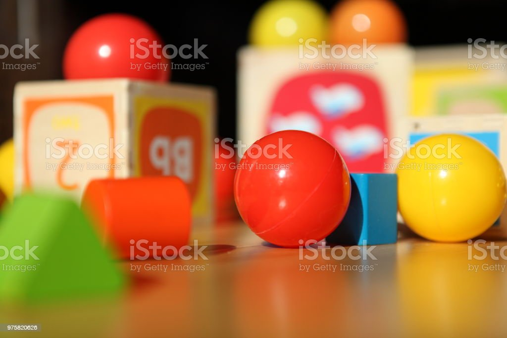 Colorful baby toys lying on a wooden floor in a room - fotografia de stock
