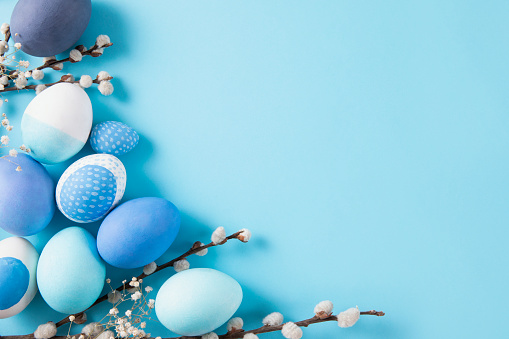 Colorful dyed easter eggs on blue background.