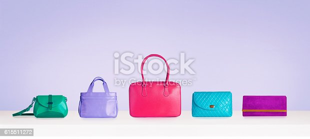 istock Colorful bags and purses isolated on purple background with copyspace. 615511272