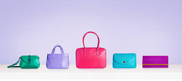 colorful bags and purses isolated on purple background with copyspace. - leder handtaschen damen stock-fotos und bilder