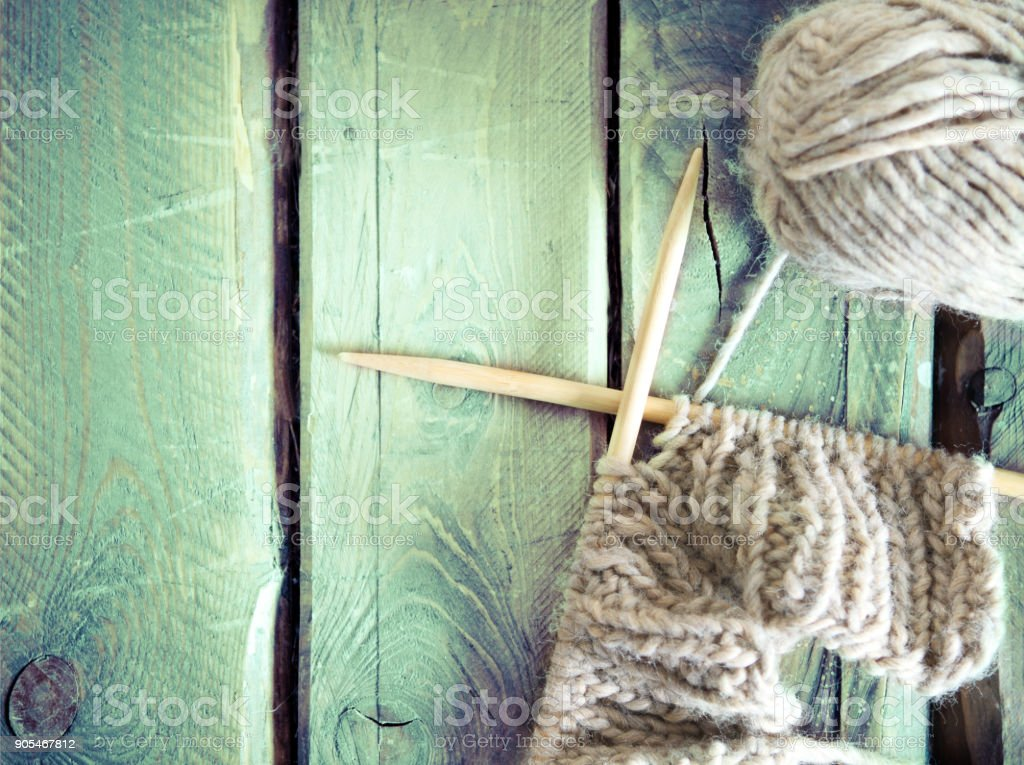 Colorful ball of yarn and knitting on a wooden table stock photo