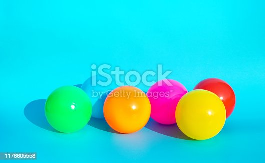 945748362istockphoto Colorful balloon with shadow on blue color background.party and celebration concepts 1176605558