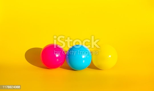945748362istockphoto Colorful balloon with shadow on yellow color background 1176624068