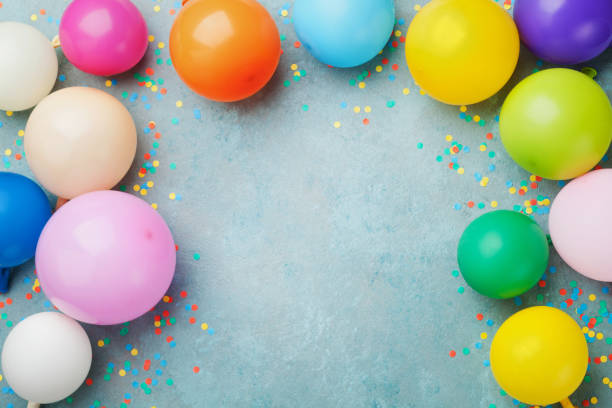Colorful balloons and confetti on blue table top view. Festive or party background. Birthday greeting card. stock photo