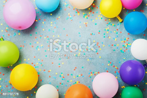 istock Colorful balloons and confetti on turquoise table top view. Birthday, holiday or party background. Flat lay style. 831732778