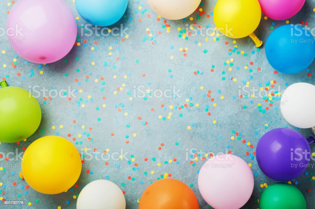 Colorful balloons and confetti on turquoise table top view. Birthday, holiday or party background. Flat lay style. stock photo