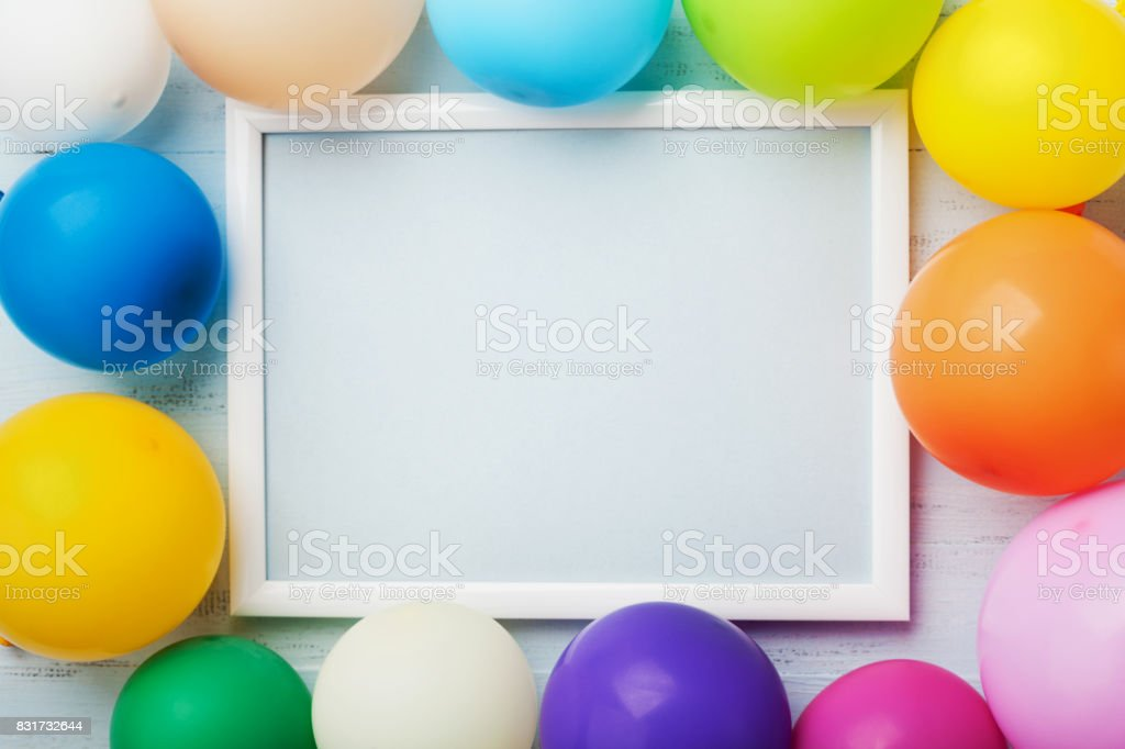Colorful balloons and white frame on blue wooden table top view. Mockup for planning birthday or party. Flat lay style. stock photo