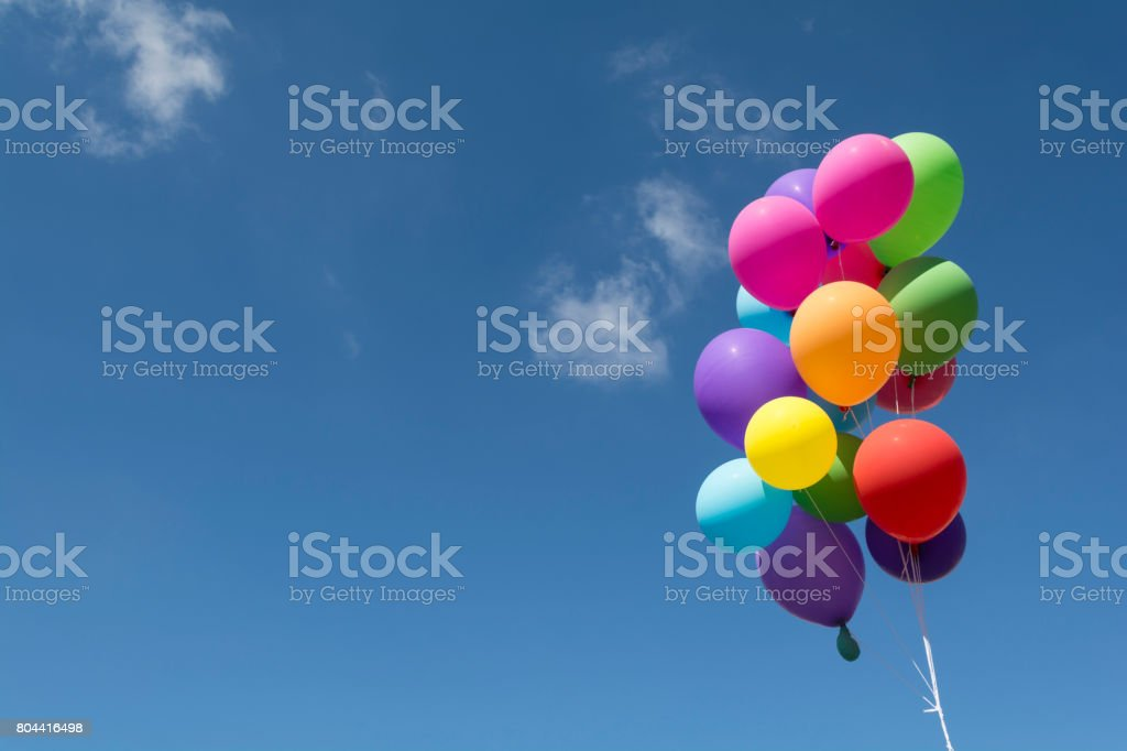 Colorful balloons flying in the blue sky stock photo