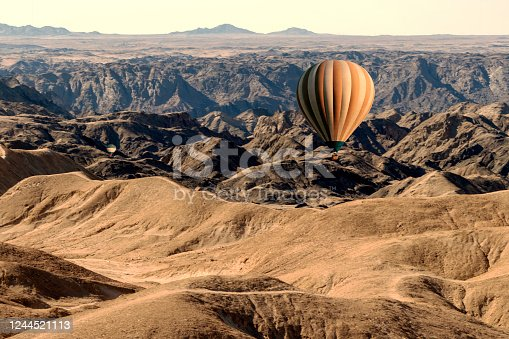 530709531 istock photo Colorful balloons flying over the moon valley mountain. Africa. 1244521113