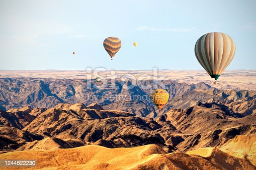 530709531 istock photo Colorful balloons flying over the moon valley mountain. Africa. 1244522230