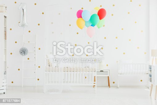 istock Colorful balloons in baby room 871577684