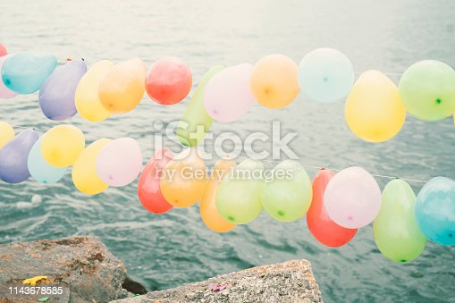 istock Colorful balloons on blue sky and sea background. 1143678585