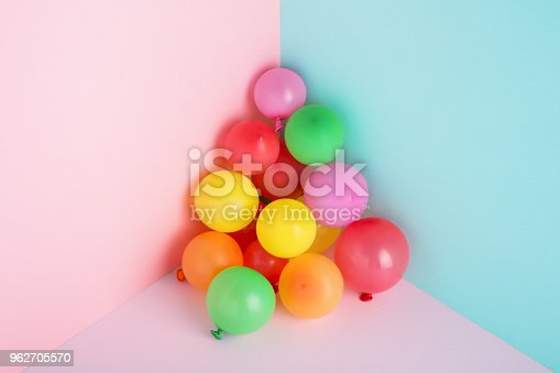 945748362istockphoto Colorful balloons on minimal trendy pastel background for party. 962705570