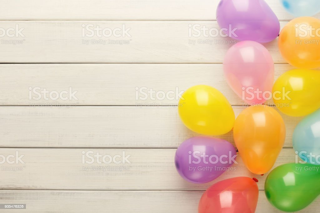 Colorful balloons on white rustic wood, birthday background, top view stock photo