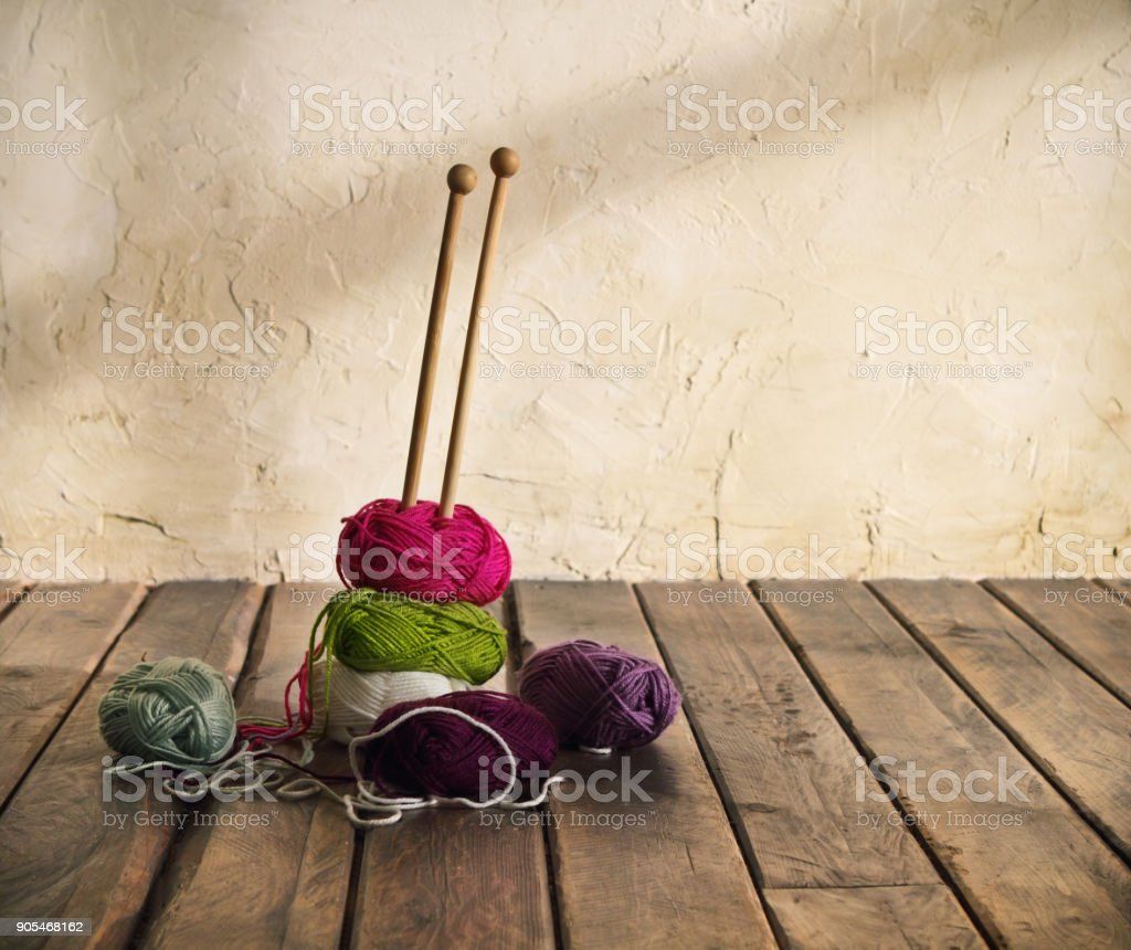 Colorful balls of yarn on a wooden table stock photo