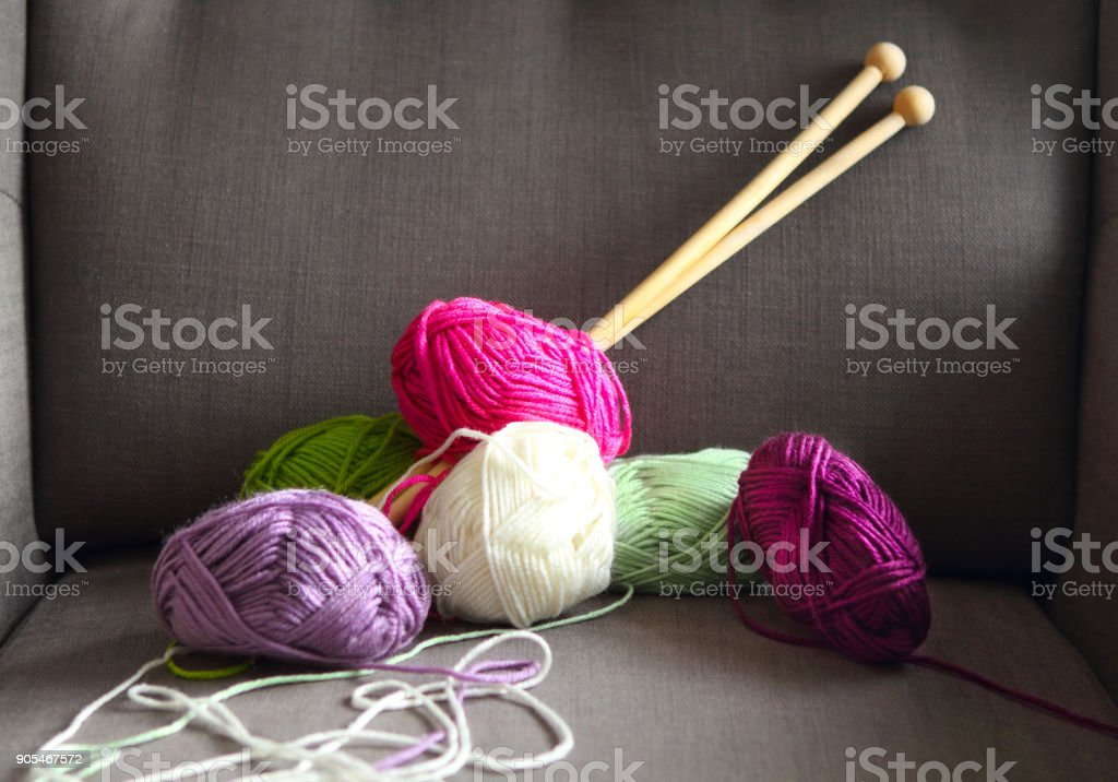 Colorful balls of yarn on the gray armchair stock photo