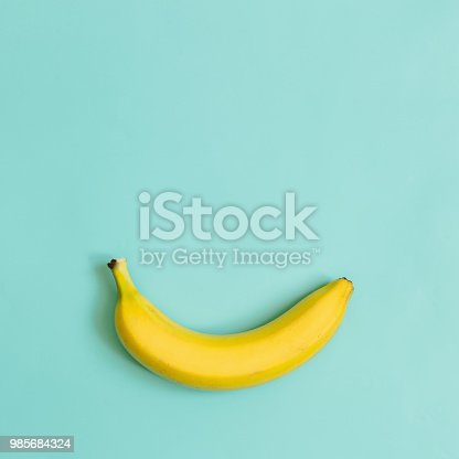 One, single banana on cyan blue, green background. Room for text. Minimalist concept.