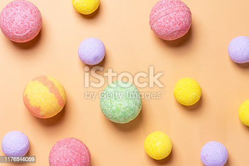 Colorful bath bombs on a pastel orange background, top view, flat lay. Spa concept.
