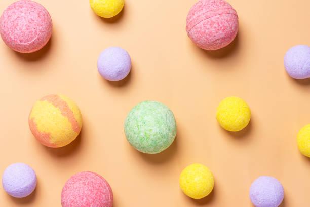 파스텔 오렌지 배경에 다채로운 목욕 폭탄 - 욕조 뉴스 사진 이미지