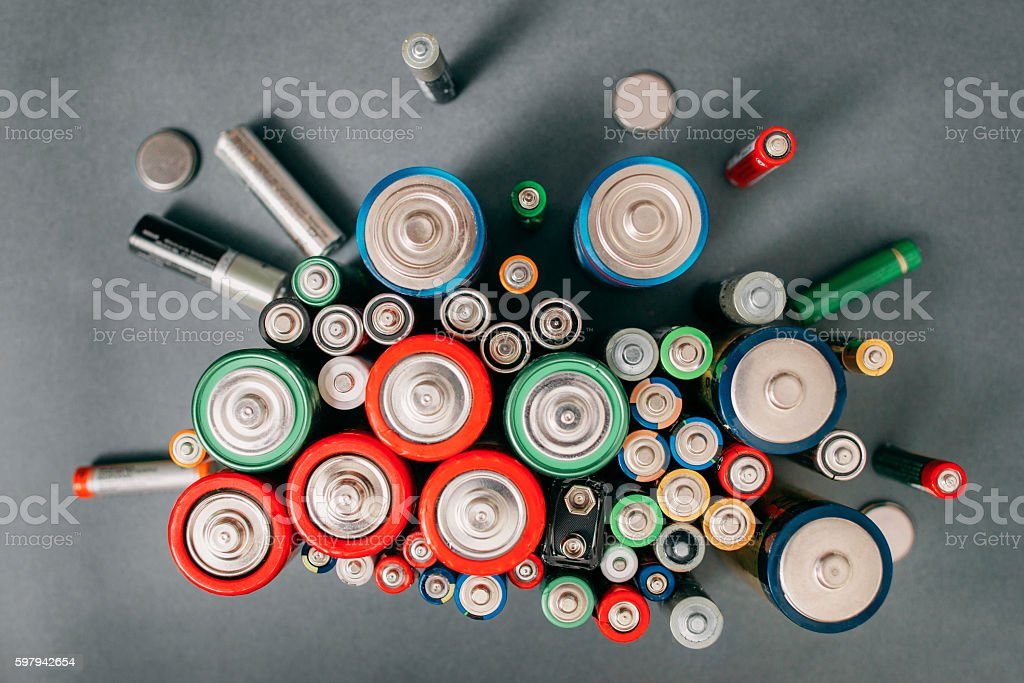 Colorful batteries on gray background, top view stock photo