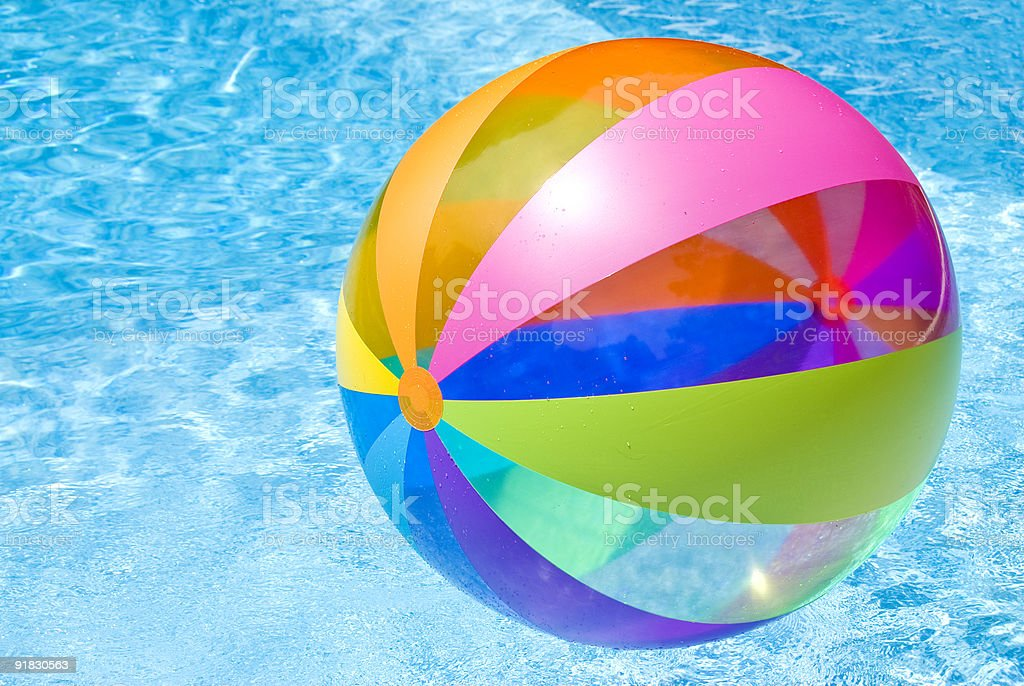 Colorful beach ball floating on a pool royalty-free stock photo