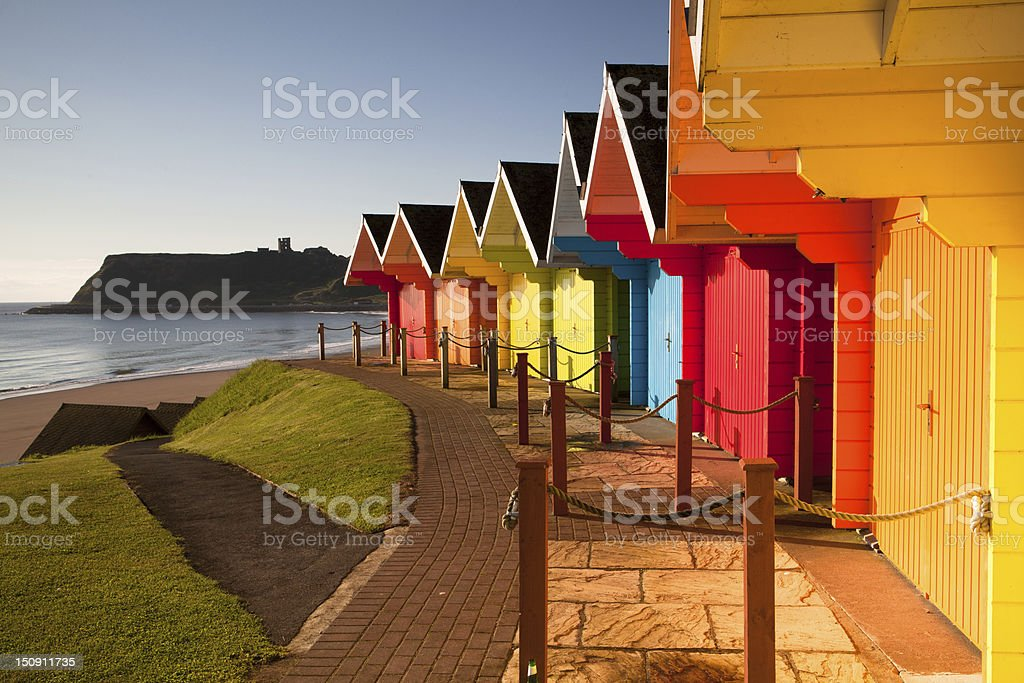 Colorful beach huts near ocean Beach huts at sunrise in Great Britain Beach Stock Photo