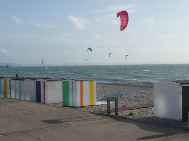 Colorful beach huts on the beach of Le Havre with kitesurf wings in the background, Normandy, France Designed during the emergence of marine baths to preserve good morals as well as to protect themselves from freshness, beach huts are now an integral part of the cultural heritage of Le Havre. le havre stock pictures, royalty-free photos & images