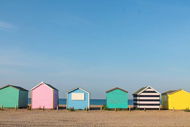 Colorful beach huts on the seafront Colorful row of beach huts on the beach beach hut stock pictures, royalty-free photos & images