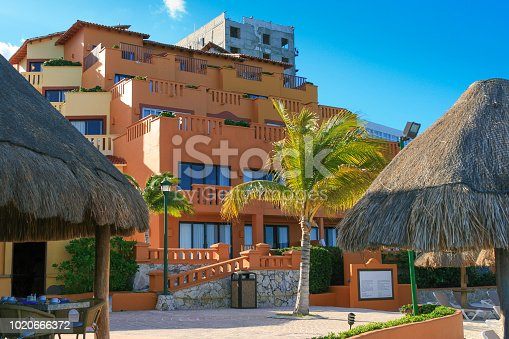 Colorful Beach Resorts at Caribbean Sea with Blue Sky, Cancun, Mexico. Tents with thatched roof and palm trees are in the image.