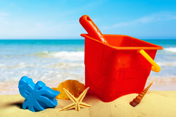 colorful beach toys on sand stock photo