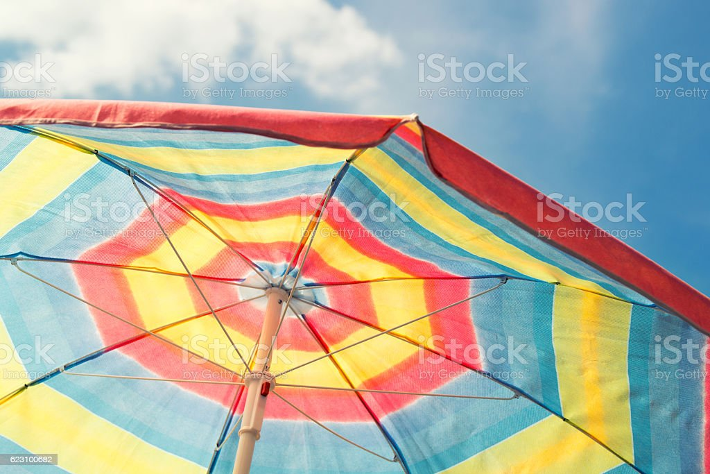 Colorful beach umbrella against blue sky, vintage filter stock photo