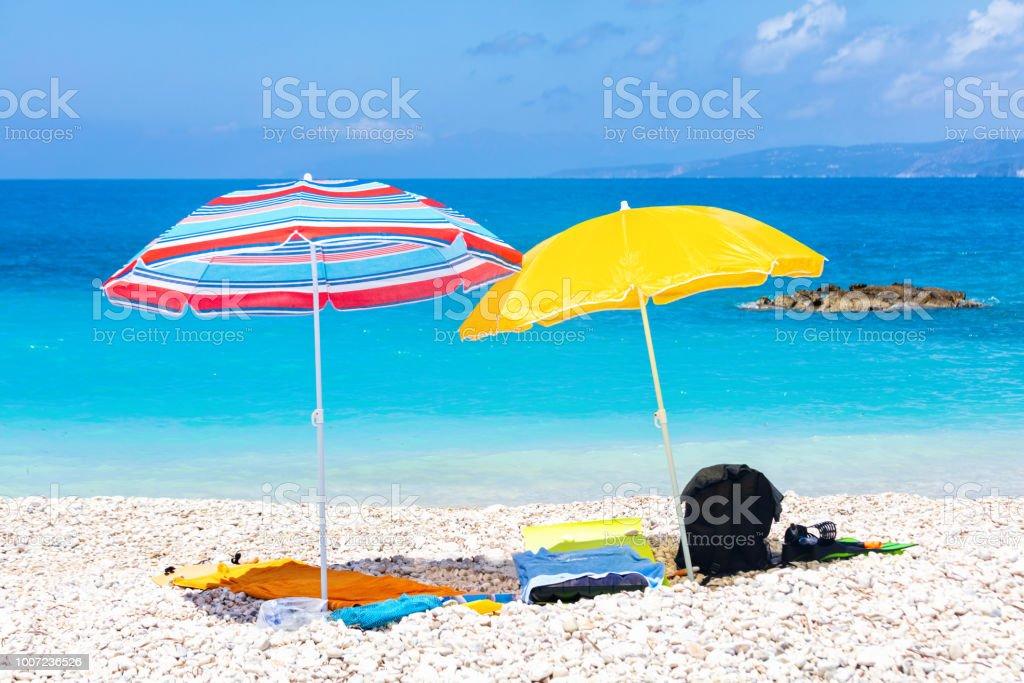 Colorful beach umbrellas by the blue sea stock photo