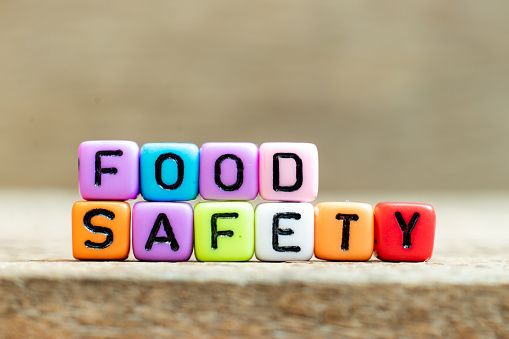 Colorful bead with black letter in word food safety on wood background