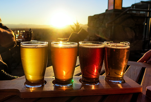 A colorful beer flights is illuminated against a bright sunset.  4 glasses of different beers are set on a wooden board and table outside.