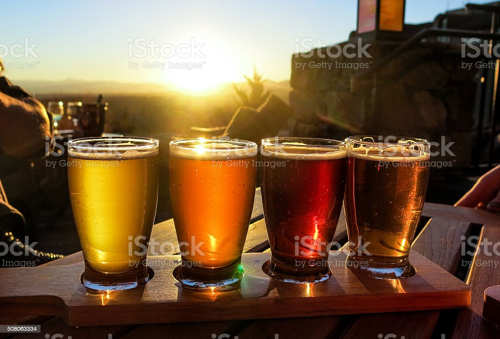 Colorful beer flight on a wooden table stock photo