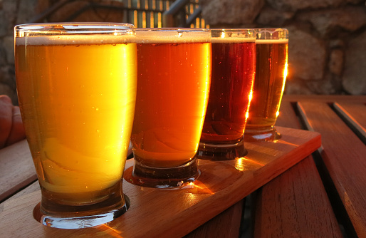 Beer flight with yellow, orange, and brown hues.  Different flavors and types of beers.