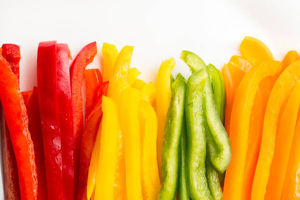 Colorful Bell Peppers Red, Orange, Green and Yellow Bell Peppers, Sliced, on a white background yellow bell pepper stock pictures, royalty-free photos & images