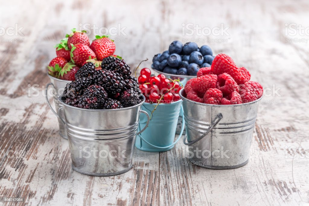 Colorful berries assortment in tin cans on rustic wooden table stock photo