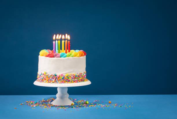colorful birthday cake over blue - день рождения стоковые фото и изображения