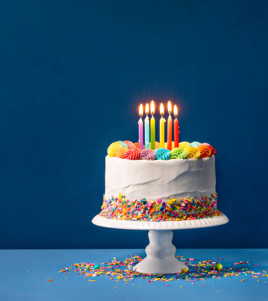 Colorful Birthday Cake over Blue Birthday cake with rainbow icing, colorful Sprinkles and lit candles over a blue background. birthday cake stock pictures, royalty-free photos & images