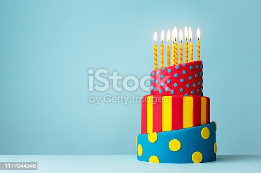 Colorful topsy turvy birthday cake with candles