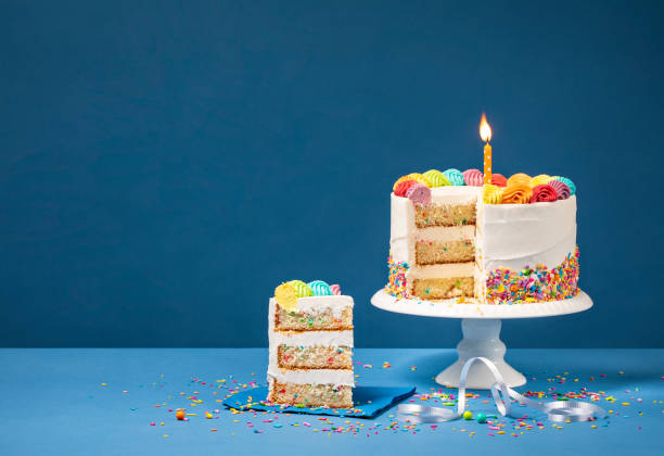 colorful birthday cake with slice and sprinkles - кусок торта стоковые фото и изображения