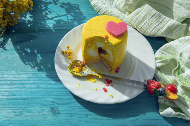 colorful bitten off yellow mini cake on white plate with spoon decorated with fruits - mimosa cake foto e immagini stock