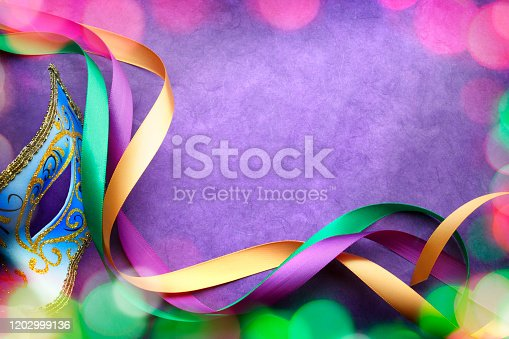 Colorful blurred lights surround a Mardi Gra mask and ribbons on a purple background that provides ample room for copy and text.