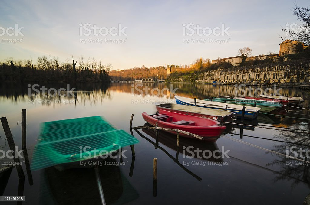 colorful boats and old stone dam reflected in water stock photo